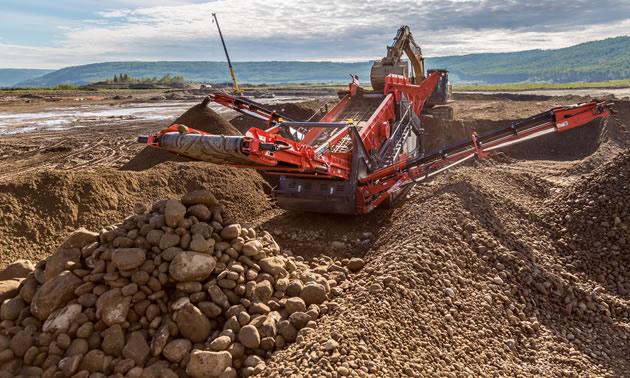 A piece of heavy equipment is moving piles of dirt and rocks.