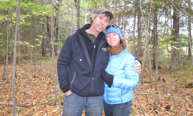 A man and woman standing outside in the forest