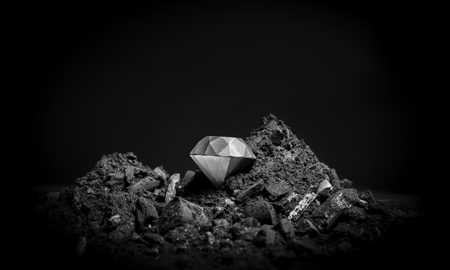 A silvery-coloured diamond on a pile of dark, fine rock rubble