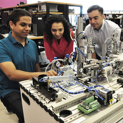 Instructor Amr Marzouk (L) shows new state-of-the-art industrial training assembly line equipment to students Anahita Mahmoodi and Mouataz Kaddoura.