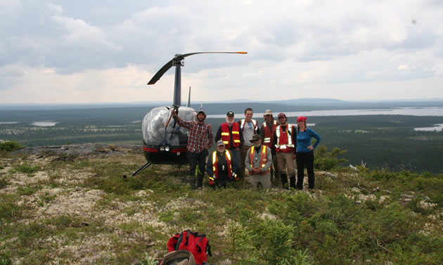 Stelmine Canada group shot, standing in front of a helicopter.