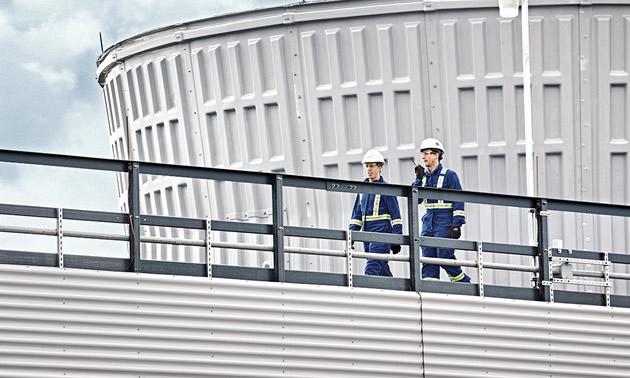 Two trades workers walking along a steel walkway.