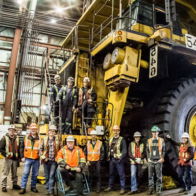 Picture of group of Teck employees standing in front of large machine.