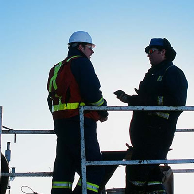 Two workers standing at a railing talking.