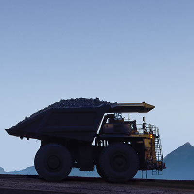 Silhouette of mining truck against blue sky.