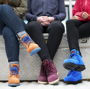3 women sitting on a bench, all wearing different coloured Tiga Workwear's boots.