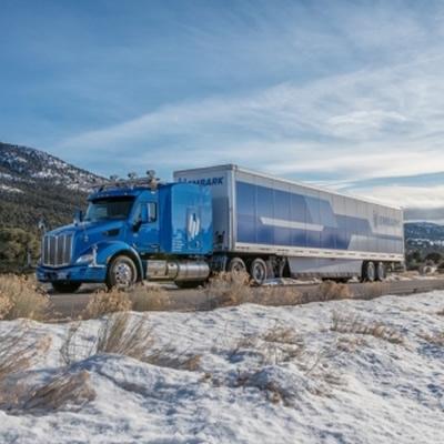 A long-haul truck on a snowy day.