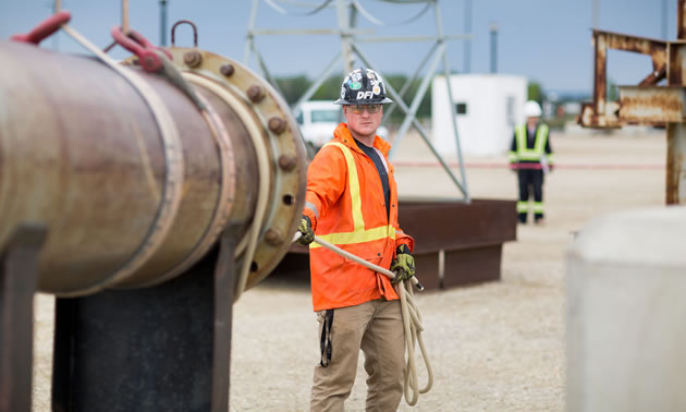 A young worker is standing by a pipeline.