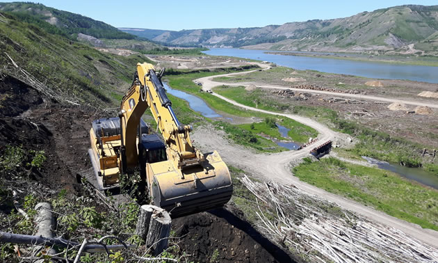 Pictured is a piece of construction equipment in the foreground with a view of the Peace River Valley beyond.
