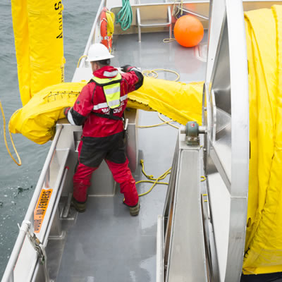 Worker deploying spill response equipment.