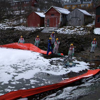 WWF staff and volunteers practicing the use of a boom to catch oil spills on water.