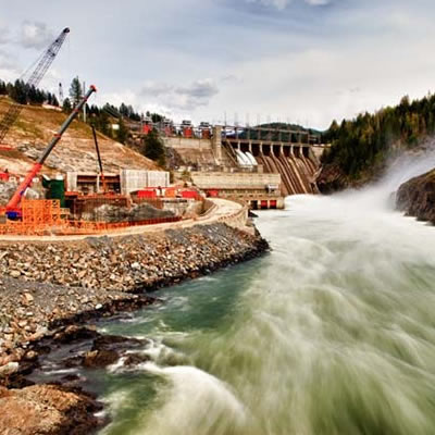 A view showing a rushing river, with dam construction and equipment along the bank.