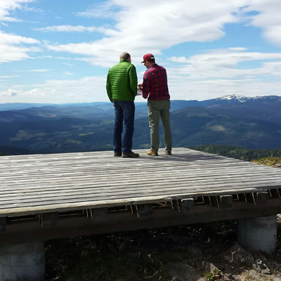 Two men standing on wooden platform with backs to the camera, looking over map in hand with view of the Shovelnose gold property in distance.