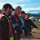 Four men wearing field gear inspect drill core samples