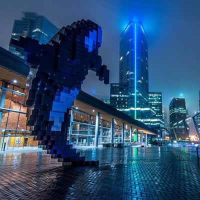 A cityscape in shades of blue, tall towers in background, an orca whale sculpture in foreground.