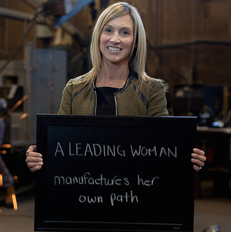 Alicia Woods, General manager of Marcotte Mining standing holding a sign that says
