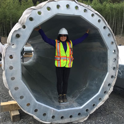 Alicia Du, general manager of HJT Steel Tower North America Co. Ltd., is standing inside a large steel cylinder.
