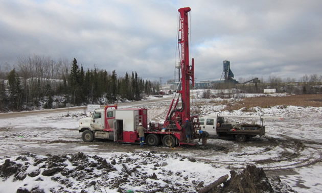 A large mining drill situated on a snowy field
