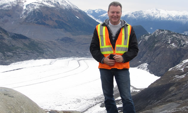 Bill Robertson is standing on a mountain and checking structure locations prior to construction at the Brucejack Gold Mine.