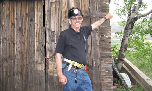 Bob Moffatt, standing in front of weathered building.