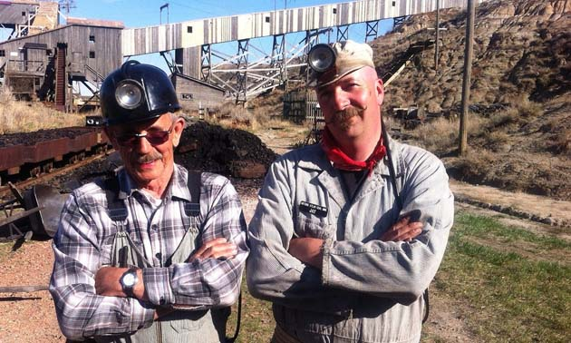 Bob Moffatt and Jay Russel, Executive Director at Atlas Coal Mine, pose in mining clothes on the site.