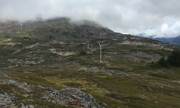 Completing the Brucejack transmission towers ranks as one of Alicia Du's proudest moments. The photo shows the transmission line crossing rocky terrain.
