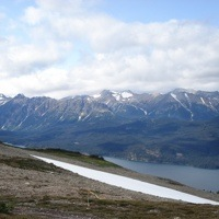 A photo of a possible new mining area, rocky slope in the forground, and a lake and mountains in the background.