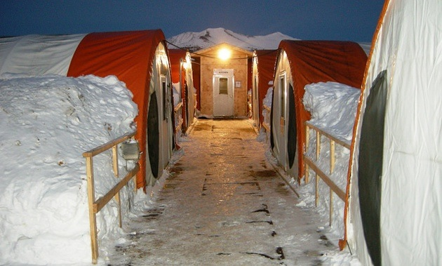 A photo of banks of snow against 4 long tents at the Selwyn Project camp.