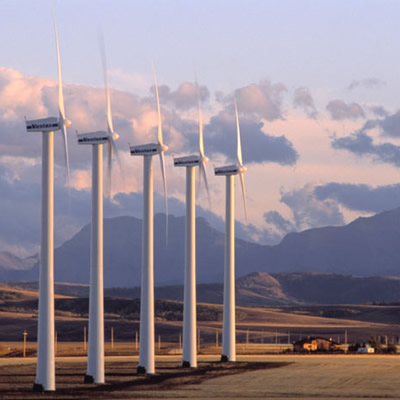 Picture of wind turbines in prairie setting, with distant mountains in background.