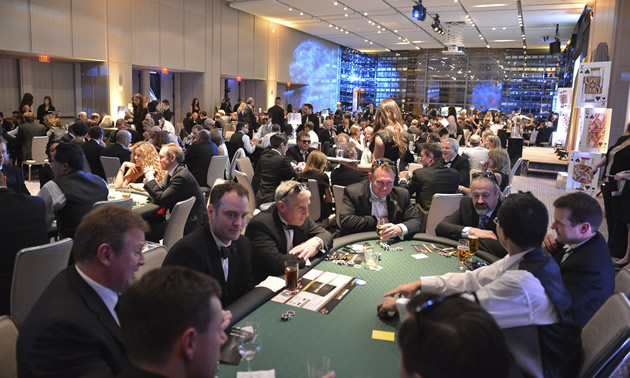 a crowd of well-dressed men and women around a casino card table
