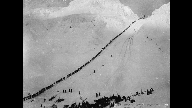 Miners ascending the steep, snowy summit of Chilkoot Pass.