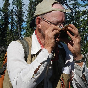 A man checking out an ore sample with a magnifying glass.