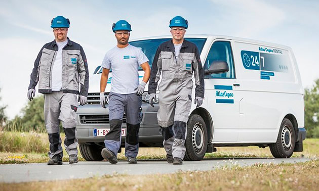 Picture of three men walking in front of Copco vehicle.