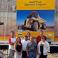 A group of haul truck operator graduates standing by the haul truck mobile simulator.