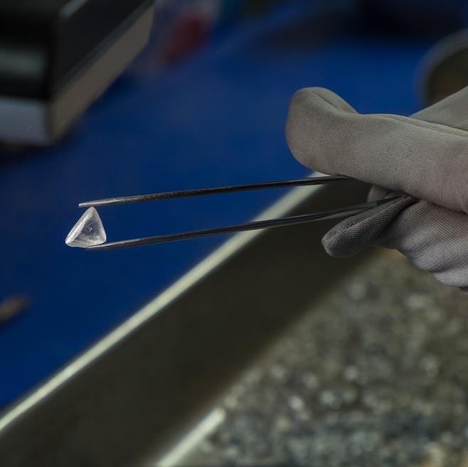 A large diamond is being held in tweezers.