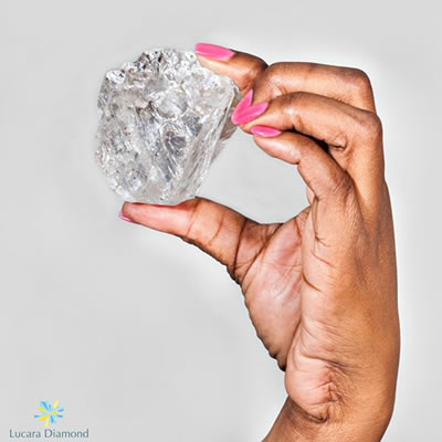 A close-up picture of a diamond held in a woman's hand.