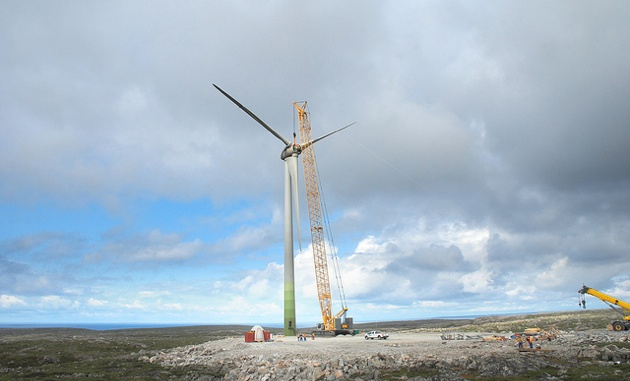 A crane is next to the wind turbine, setting it up.