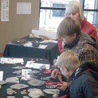 2 children looking at a display with interest at the Minerals South Conference.