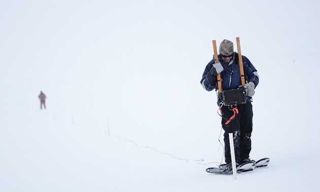 2 men walking on the snow with metal exploration equipment.