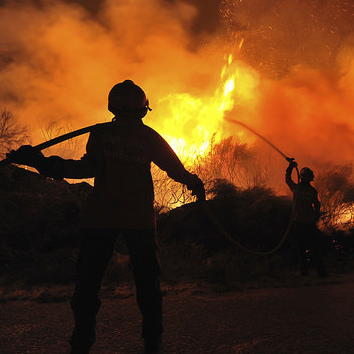 A silhouette of a firefighter in front of a blaze.