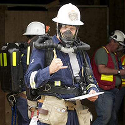Fireman wearing respirator and making the 'thumbs up' sign