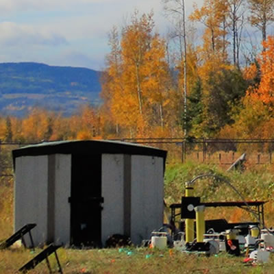 Autumn trees in background, distant mountain, equipment and tools in foreground of picture.