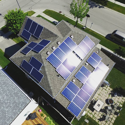 Birds-eye view of top of house equipped with solar panels.