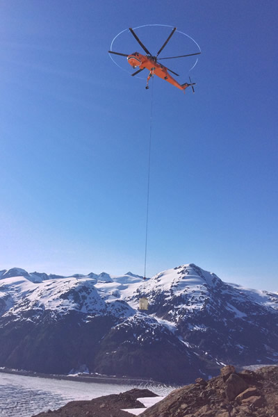 An air crane is transporting concrete to structure sites at the Brucejack Mine. The Salmon Glacier can be seen in the background.