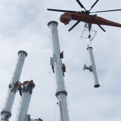 A steel pole A-frame transmission line tower is being installed with an air crane.