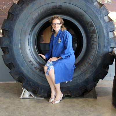 Jennifer Beaudry, sitting on large tire.