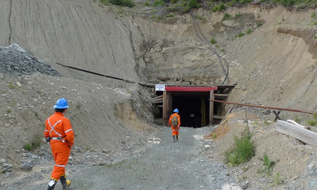 East portal into the Lexington Mine, workers walking in.