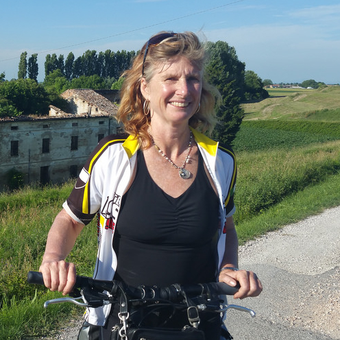 A woman (Merran Smith) on a bike smiling as she waits at the side of a road