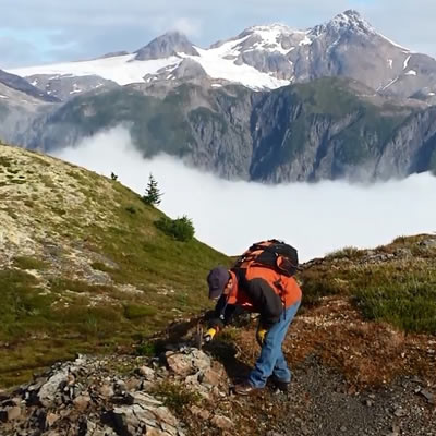 A geologist examining rocks on a mountainside.