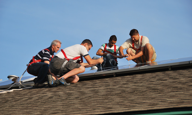 Four men on a roof working on an equipment installation.